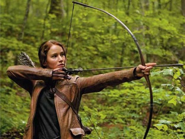 Jennifer Lawrence mostrando suas habilidades com o arco e fecha em Jogos Vorazes.